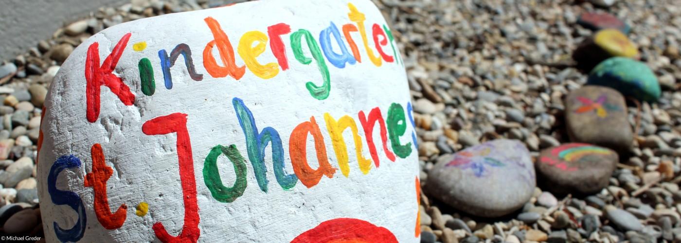 """Ein Stein mit Regenbogen und der Aufschrift """"Kindergarten St. Johannes"""""""